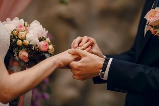 groom-putting-ring-bride-s-finger_1157-338